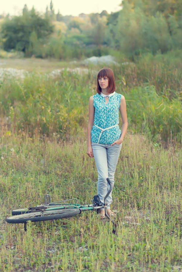 有一辆老自行车的美丽的女孩 库存图片