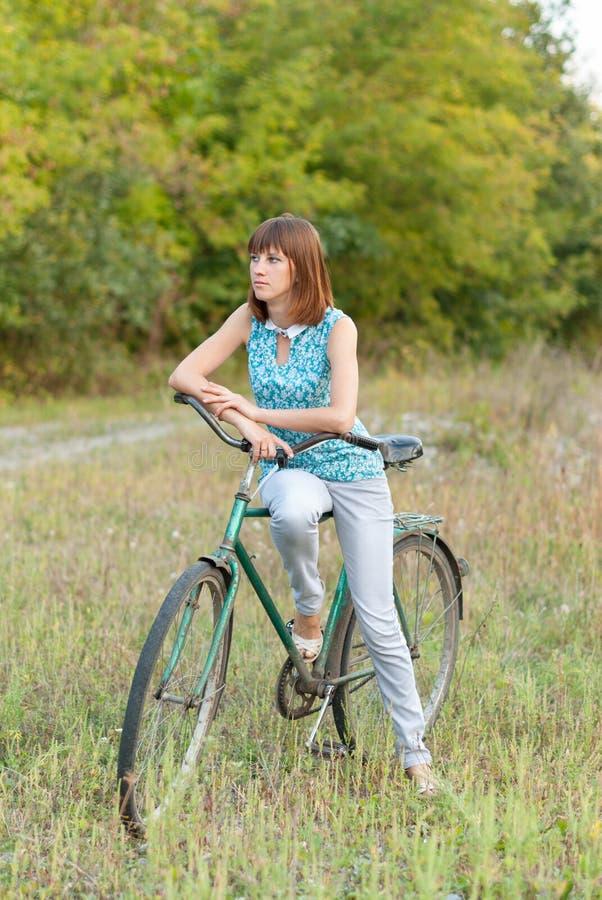 有一辆老自行车的美丽的女孩 免版税库存照片
