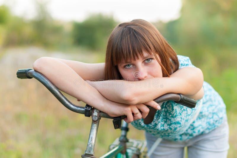 有一辆老自行车的美丽的女孩 库存照片