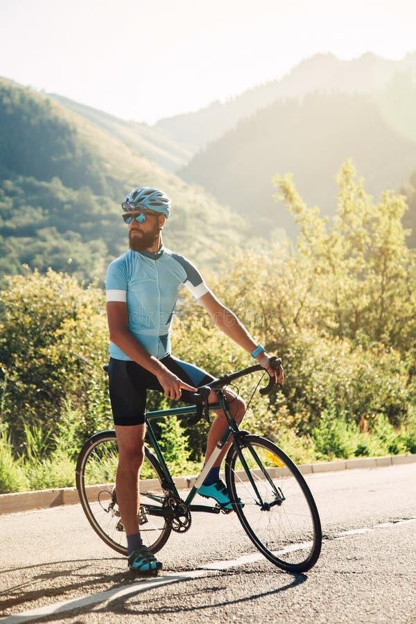 有一辆自行车的一个人在山 在用森林盖的山的路 库存图片