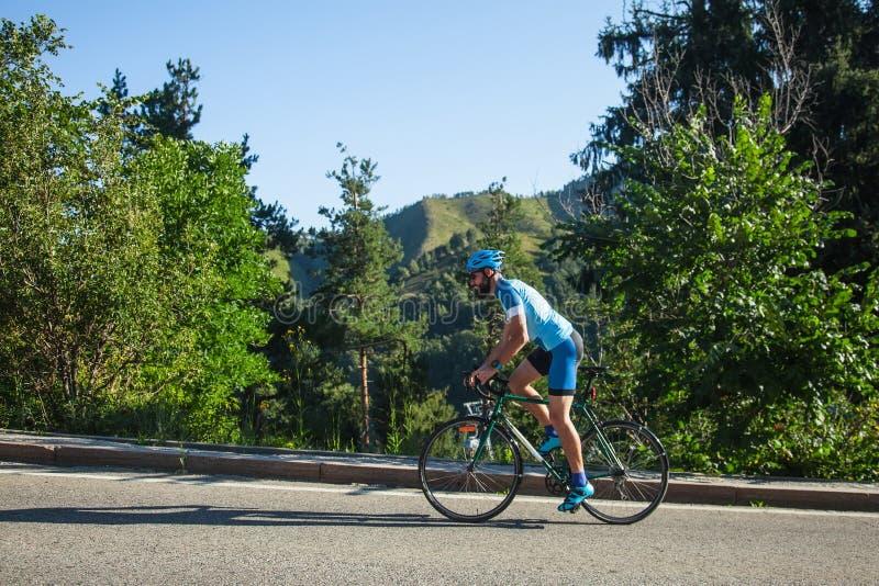 有一辆自行车的一个人在山 在用森林盖的山的路 免版税库存照片