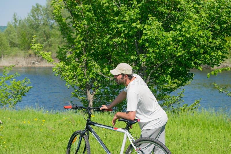 有一辆自行车的一个年轻人在自然背景 免版税库存照片