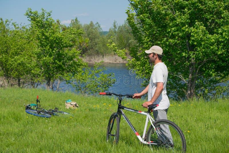 有一辆自行车的一个年轻人在自然背景 免版税库存图片