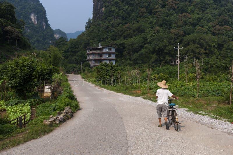有一辆自行车的人在阳朔附近镇的一条contry路在中国,亚洲,有高石灰石的在背景锐化 库存照片