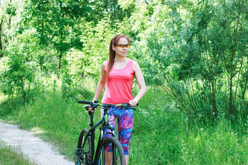 有一辆自行车的女运动员在森林里 免版税库存照片