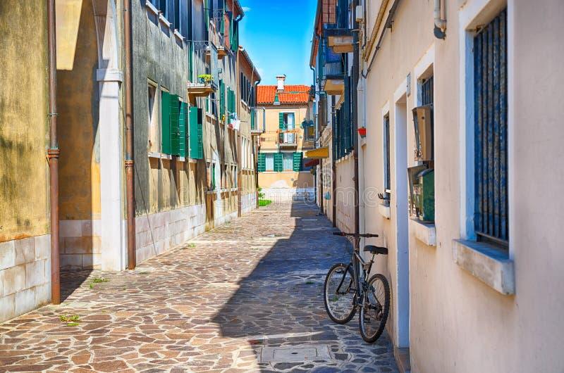 有一辆自行车的狭窄的街道早晨在穆拉诺岛海岛,威尼斯,意大利 库存图片