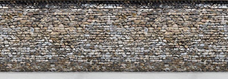 有一部分的老棕色石墙的路水平无缝 免版税库存图片