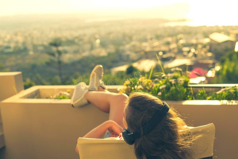 有一长发的女孩在椅子的耳机在阳台听到在日落背景的音乐的 库存照片