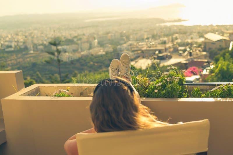 有一长发的女孩在椅子的耳机在阳台听到在日落背景的音乐的 免版税图库摄影