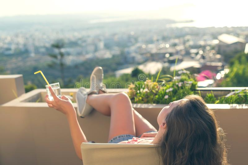有一长发的女孩在阳台的椅子听到在日落背景的音乐的 库存照片