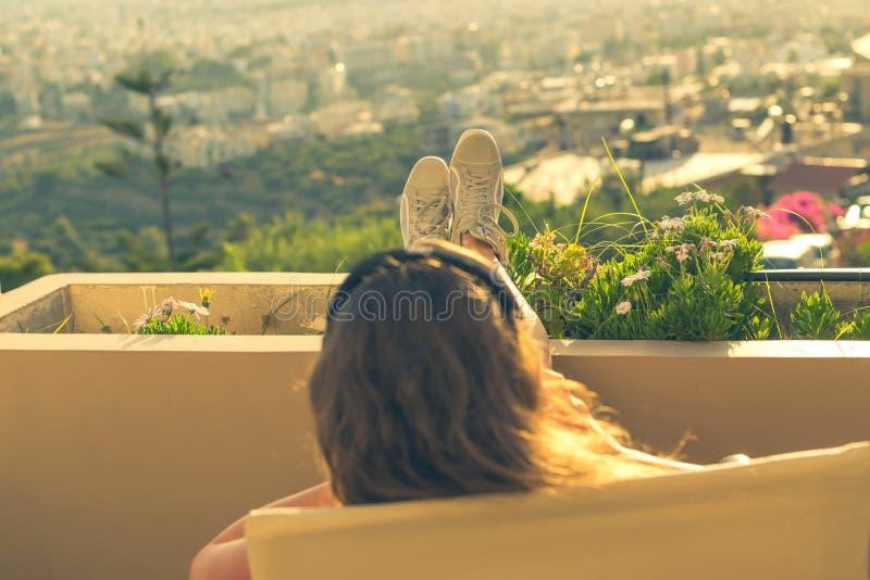 有一长发的女孩在阳台的椅子听到在日落背景的音乐的 免版税库存照片