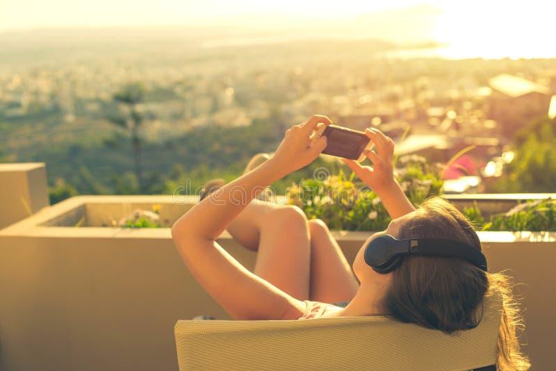 有一长发的女孩在阳台的椅子听到在日落背景的音乐的 图库摄影