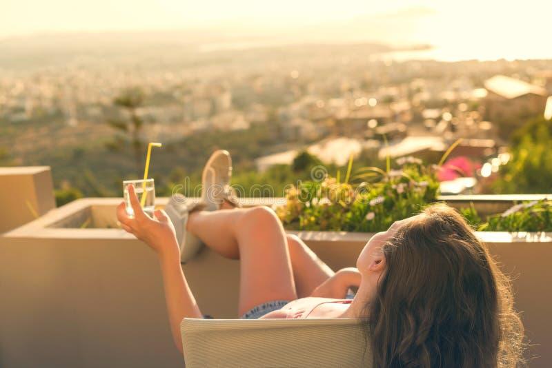 有一长发的女孩在阳台的椅子日落背景的 图库摄影