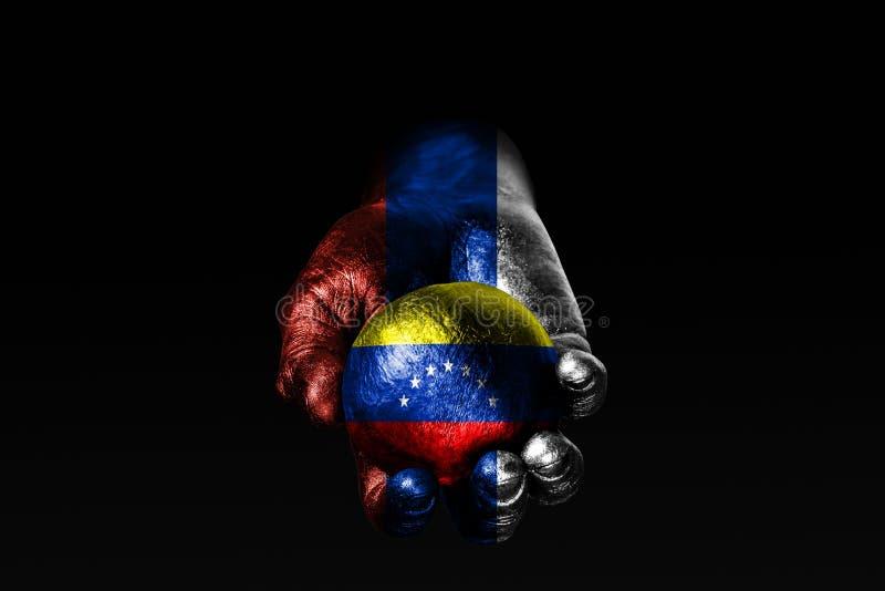 有一面拉长的俄罗斯旗子的一只手举行与一面拉长的委内瑞拉旗子的一个球,影响的标志,压力或者保护和 库存图片