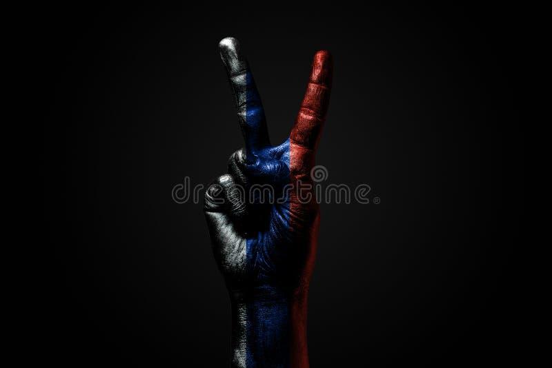 有一面拉长的俄罗斯旗子的一只手显示和平标志、和平的标志,友谊、问候和和平在黑暗 图库摄影