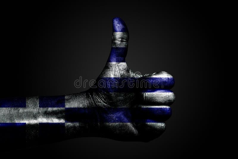 有一面拉长的希腊旗子的一只手显示标志的一个手指,成功,准备,在黑暗的背景完成的任务的标志 免版税库存照片