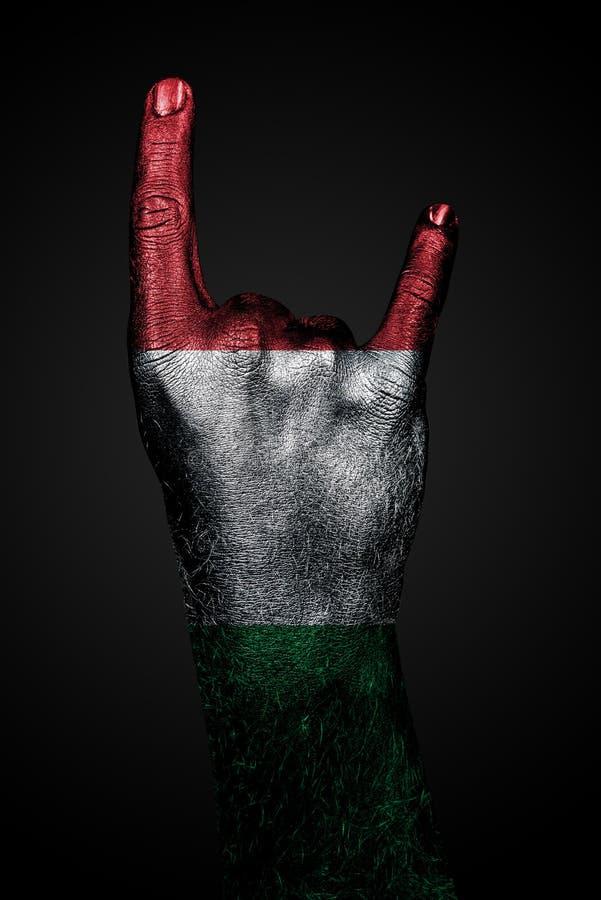 有一面拉长的意大利旗子的一只手显示一个山羊标志、主流的标志,金属和摇滚音乐,在黑暗的背景 免版税库存图片