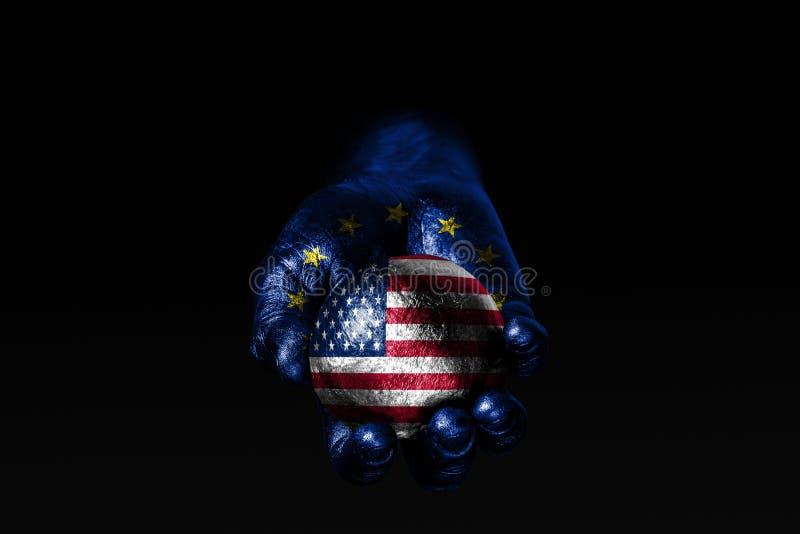 有一面拉长的欧盟旗子的一只手拿着与一面拉长的美国旗子的一个球,影响的标志,压力或者保护和保护 库存图片