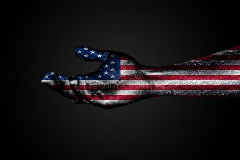 有一面拉长的美国旗子的被伸出的手,帮助的标志或一个请求,在黑暗的背景 免版税库存照片