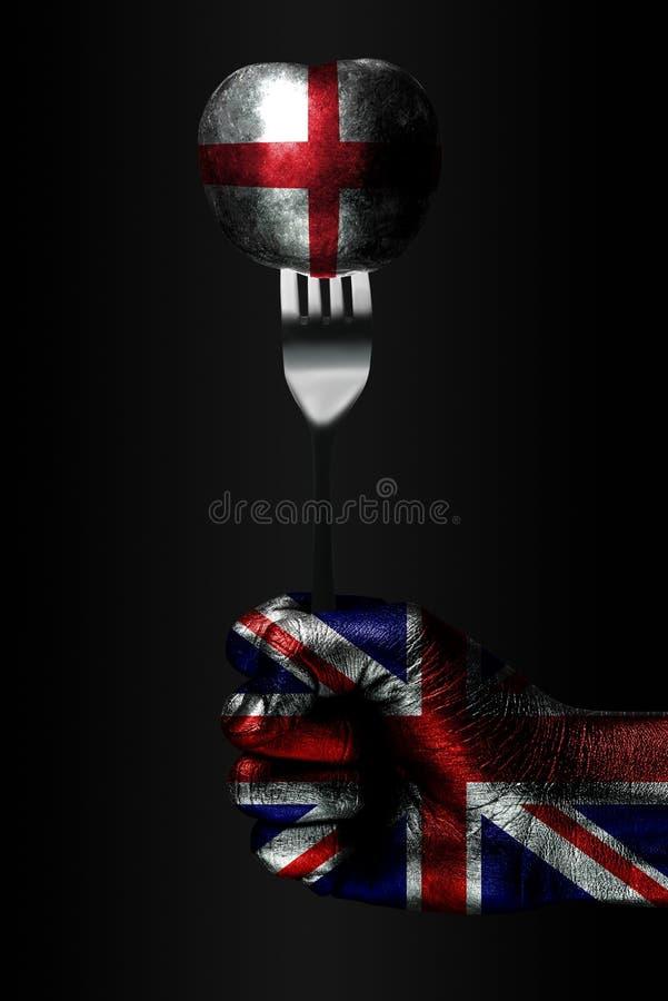 有一面拉长的英国旗子的一只手拿着一把叉子,与一面拉长的英国旗子的一个球,影响,压力的标志, 图库摄影