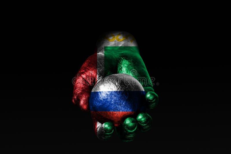 有一面拉长的车臣旗子的一只手举行与一面拉长的俄罗斯旗子的一个球,影响的标志,压力或者保护和 图库摄影