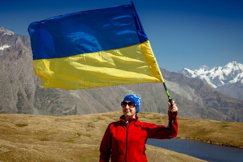 有一面旗子的女孩游人在高加索山脉 佐治亚 图库摄影