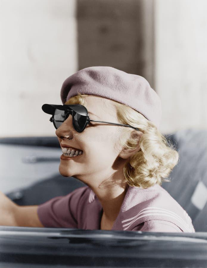 有一顶贝雷帽和太阳镜的少妇在汽车,立即使用(所有人被描述不更长生存,并且庄园不存在 一口 免版税库存图片