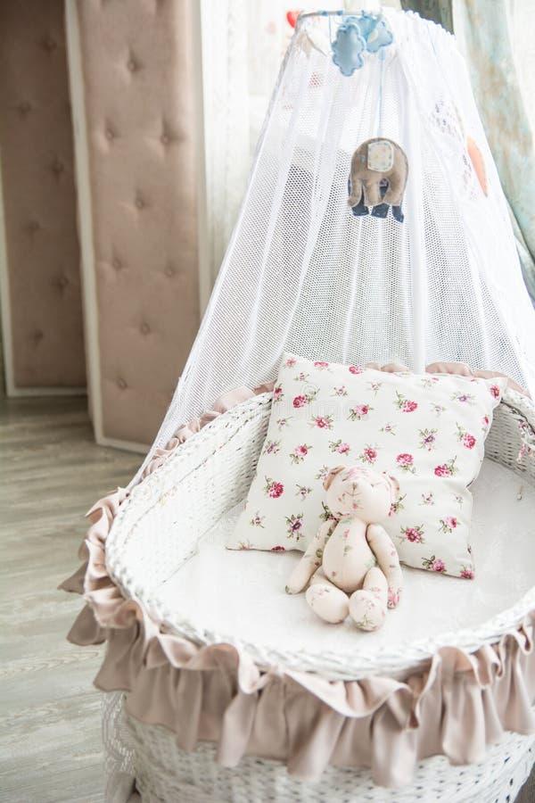 有一件柳条小儿床和女用连杉衬裤的b减速火箭的内部儿童的卧室 免版税库存照片