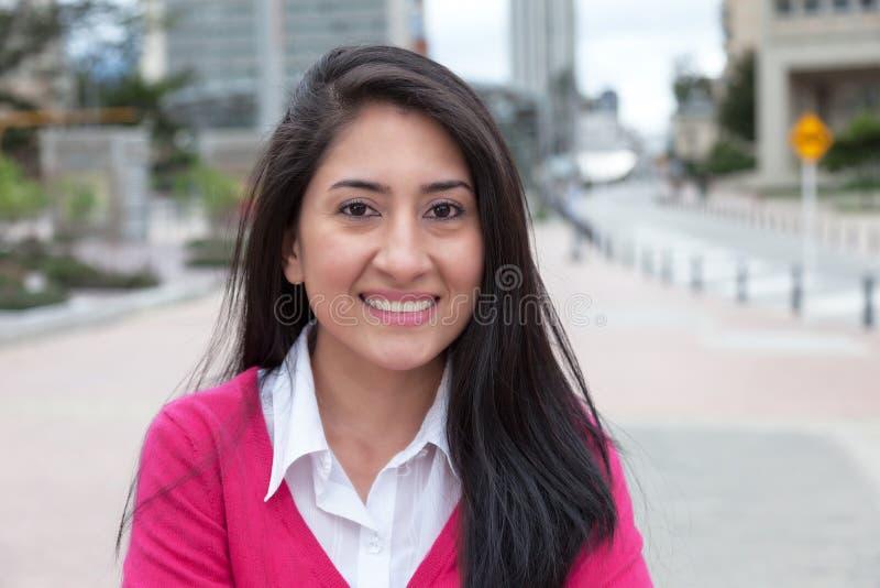 有一件桃红色背心的可爱的拉丁妇女外面在城市 库存照片