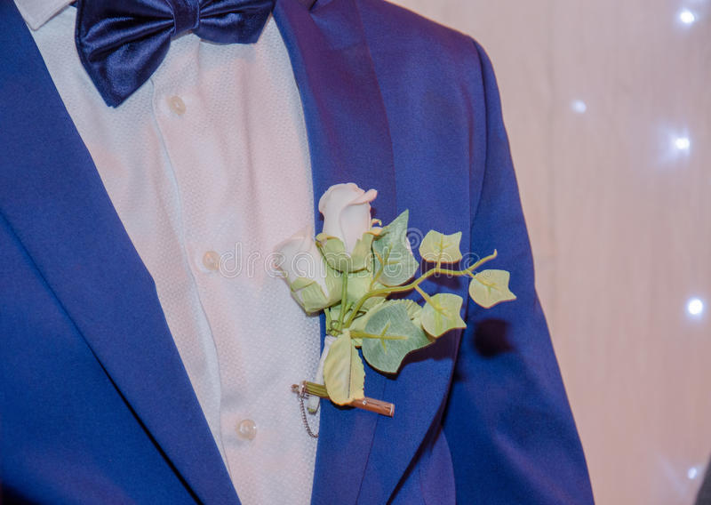 有一件白色衬衣和花的蓝色新郎夹克 库存图片