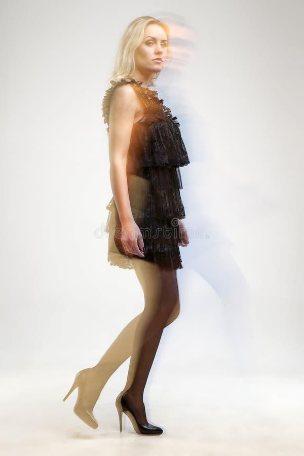 有一件礼服的美丽的妇女在移动没被隔绝的演播室的时尚射击 免版税库存图片