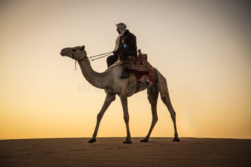 有一头骆驼的人在一片沙漠在苏丹 免版税库存图片