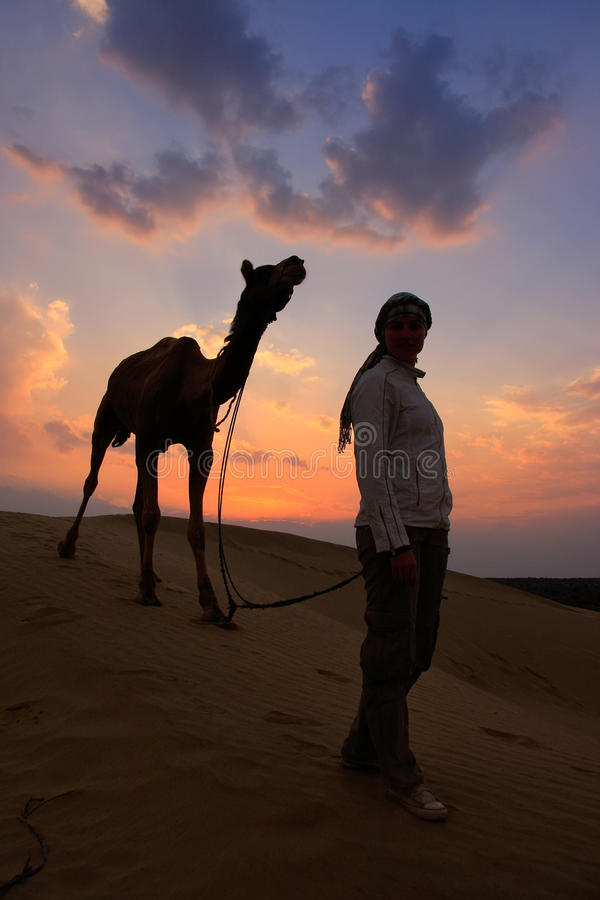 有一头骆驼的在日落,在贾伊斯附近的塔尔沙漠现出轮廓的人 库存照片