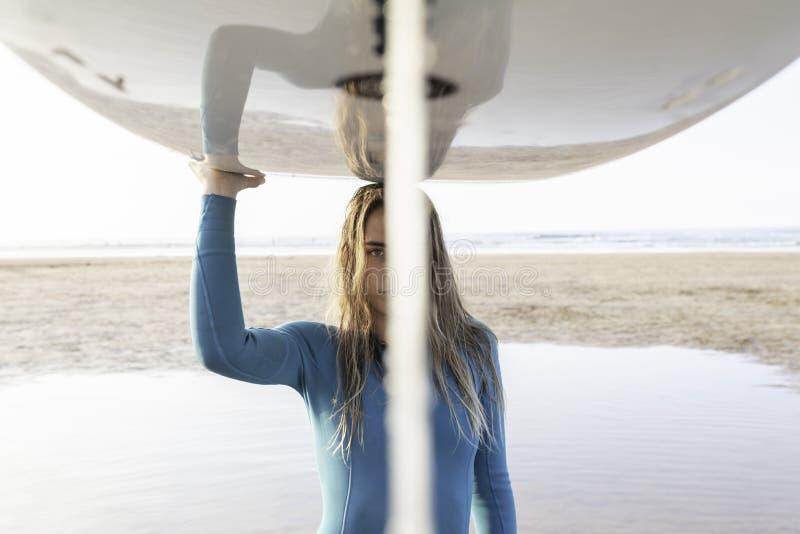 有一longboard的俏丽的海浪女孩在海滩 库存图片
