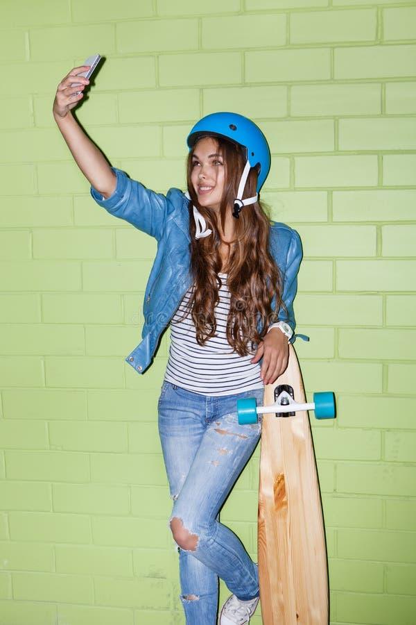 有一smartpnone的美丽的长发女孩在一块绿色砖附近 免版税库存图片