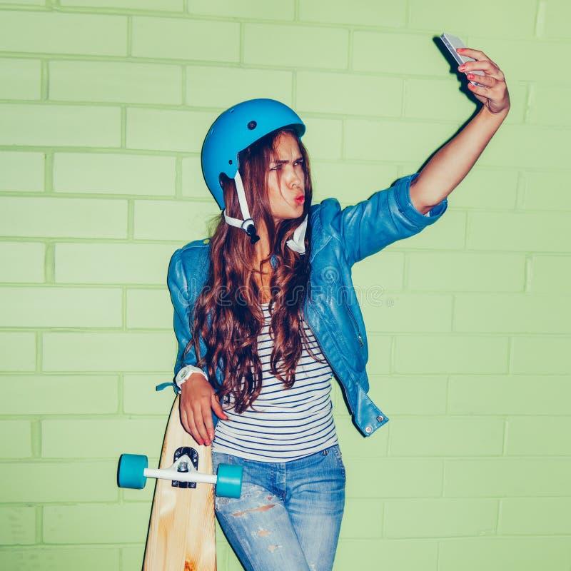 有一smartpnone的美丽的长发妇女在一块绿色砖附近 免版税图库摄影