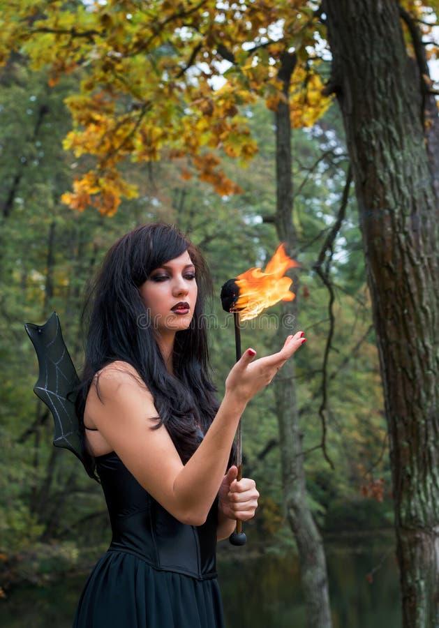 有万圣夜巫婆构成的年轻深色的妇女站立与t 免版税库存照片