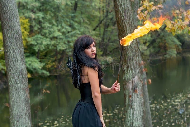 有万圣夜巫婆构成的深色的妇女站立与火炬我 免版税库存图片