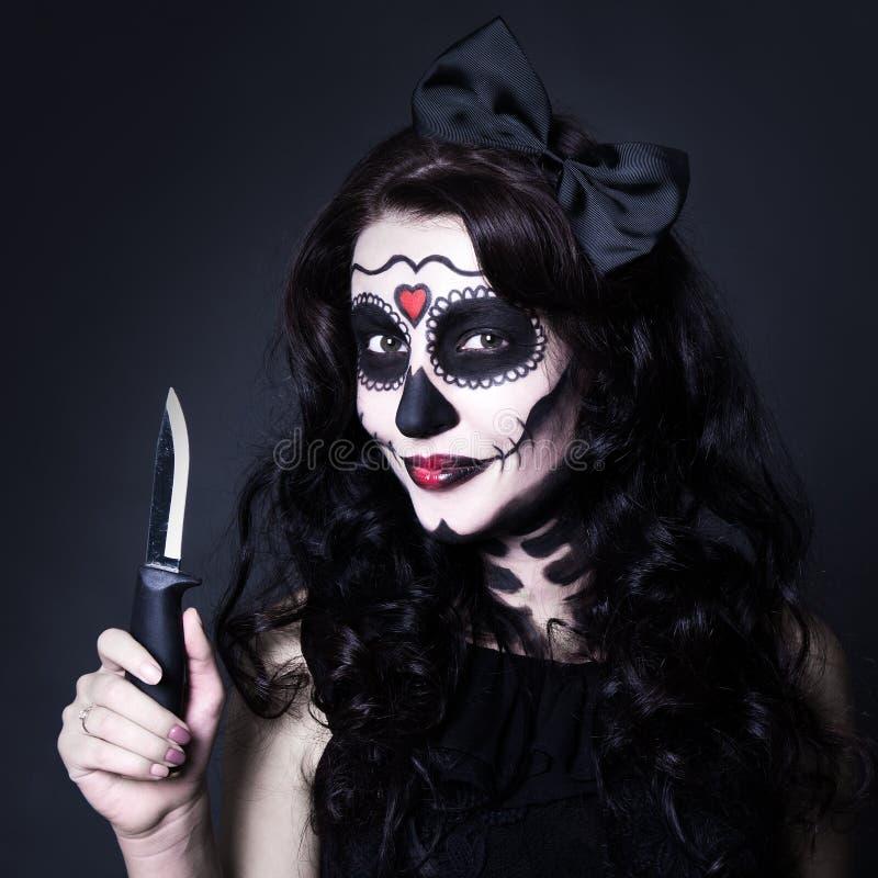 有万圣夜头骨的妇女做停滞在黑色的刀子 库存照片