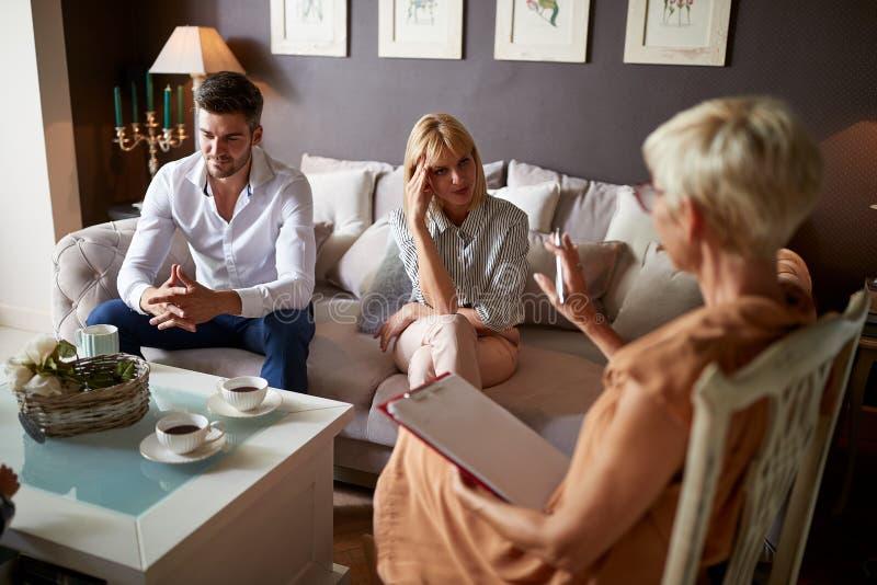 有丈夫听的心理学家的担心的妻子 免版税库存照片