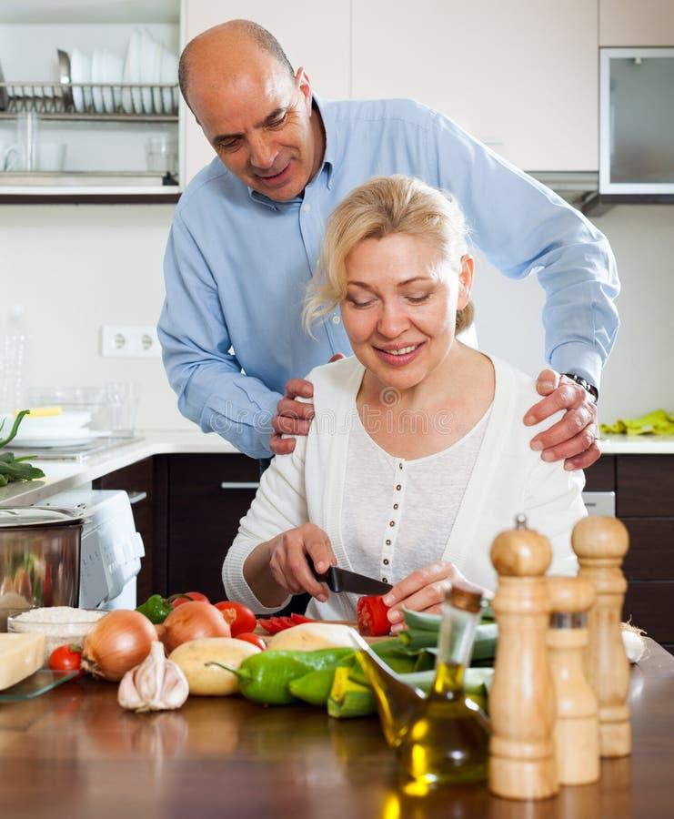 有丈夫烹调的爱恋的成熟妇女 库存照片