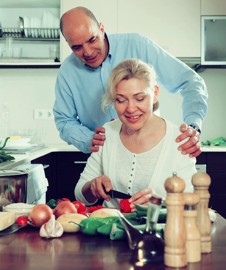 有丈夫烹调的爱恋的成熟妇女 免版税图库摄影