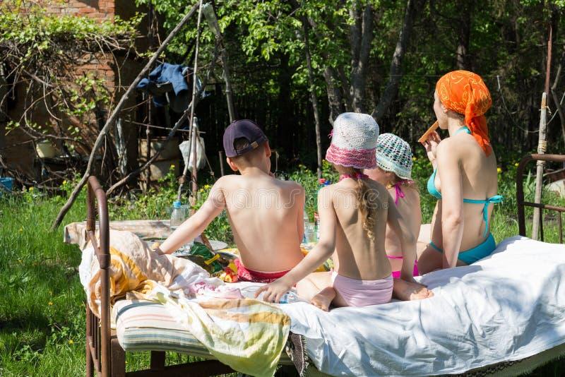 有三个孩子的女性有一顿野餐 免版税库存图片