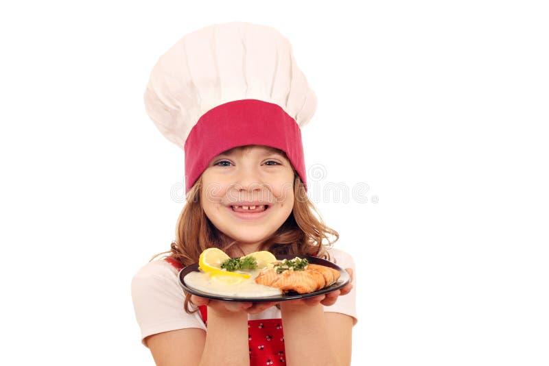 有三文鱼鱼的愉快的小女孩厨师 库存照片
