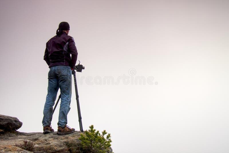 有三脚架的室外在岩石认为的摄影师和照相机 大雾在秋季乡下 在锋利的clif的人工作 库存图片