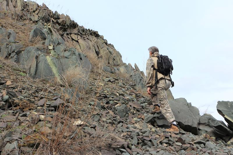 有上升在石头的背包的人到山 图库摄影