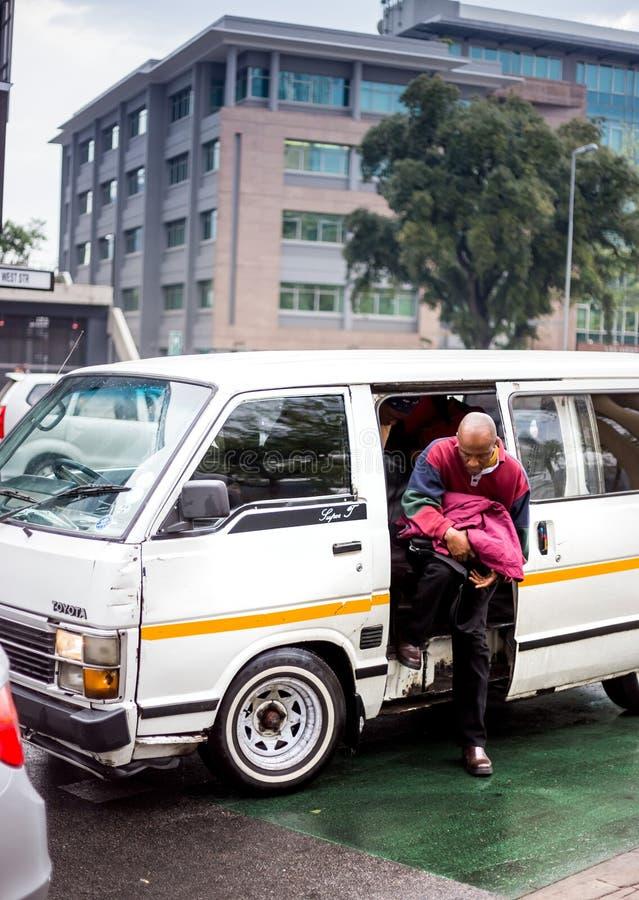 有上升的乘客的微型公共汽车出租汽车  免版税库存图片