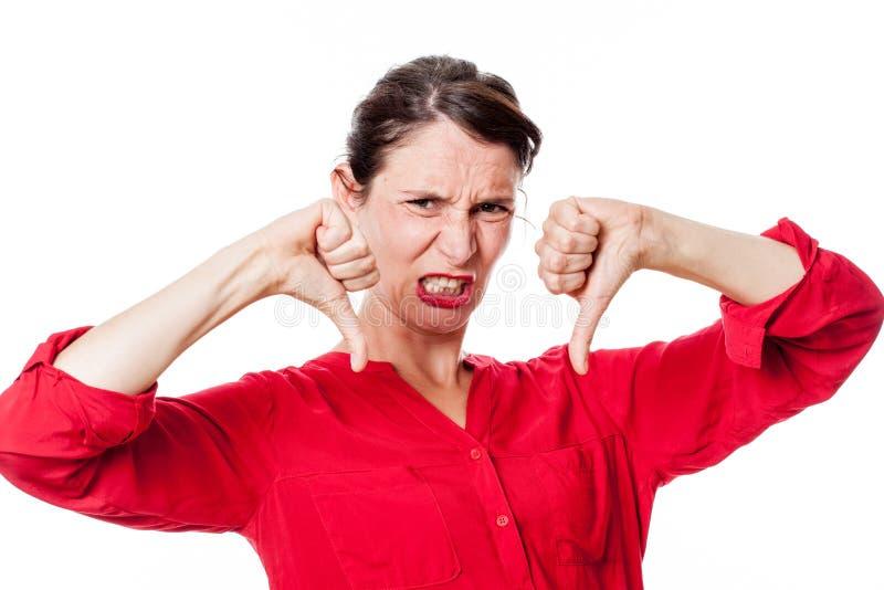 有下来研牙的失望的拇指的愤怒的少妇 免版税库存照片