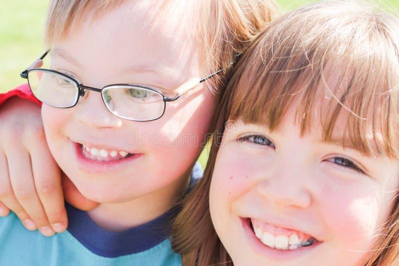 有下来综合症状的男孩与姐妹 图库摄影