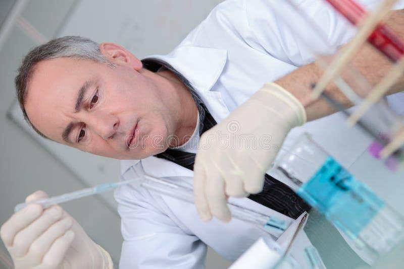 有下落液体的实验室吸移管在玻璃试管 免版税图库摄影
